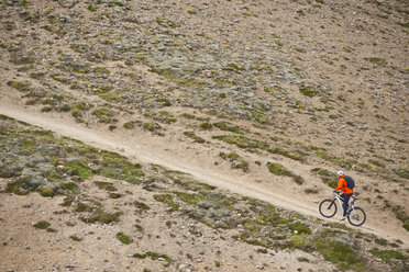 Male mountain biker cycling up steep dirt track,  Reykjadalur valley, South West Iceland - CUF38693