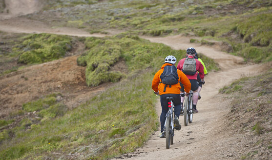 Rear view of three mountain bikers cycling through Reykjadalur valley, South West Iceland - CUF38696