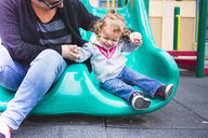 Mother and daughter going down slide in playground - ISF15635
