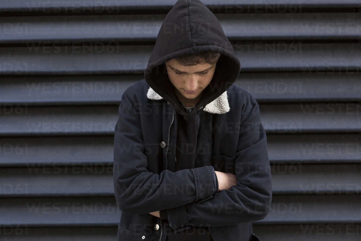 Teenage boy in front of black background wearing hooded jacket - JUNF01064 - JLPfeifer/Westend61