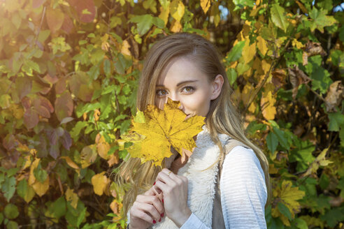 Portrait of woman with yellow autumn leaf - JUNF01070