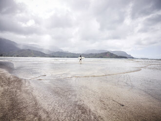 USA, Hawaii, Kauai, Hanalei Bay Resort, man on the beach with surfboard - CVF00925