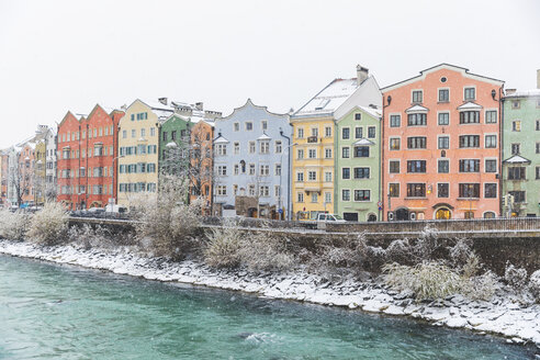 Austria, Innsbruck, row of colourful houses in winter with Inn River in the foreground - WPEF00567