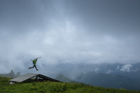 Germany, Brauneck, young hiker with hiking poles and backpack jumping in the air - LBF01997