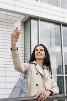 Portrait of smiling woman taking selfie with cell phone - JUNF01076