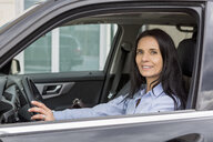 Portrait of smiling woman driving car - JUNF01079