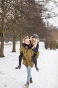 Young man giving his girlfriend a piggyback ride in winter - WPEF00571