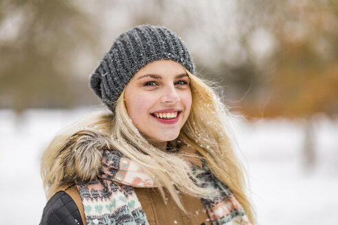 Portrait of smiling blond teenage girl in winter - WPEF00577