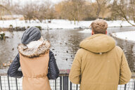 Back view of young couple standing side by side in park in winter - WPEF00580