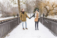 Young couple in love standing hand in hand on footbridge in a park on a snowy day - WPEF00583
