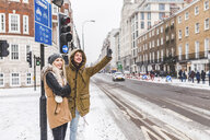 UK, London, young couple standing at roadside hailing taxi in winter - WPEF00589