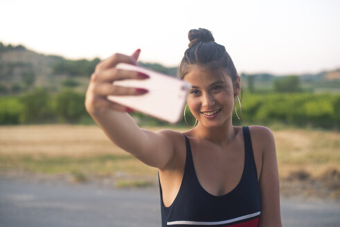Portrait of smiling teenage girl taking selfie with smartphone outdoors - ACPF00077