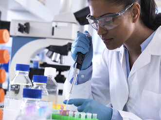 Genetic research, female scientist pipetting DNA or chemical sample into a eppendorf vial, analysis in the laboratory - ABRF00173