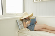 Girl in sunhat reading on holiday apartment porch seat - CUF38832