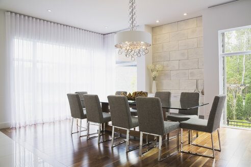 Modern interior design luxury dining room with glass dining table and grey upholstered dining chairs - ISF15806