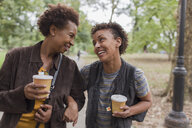 Two mature female friends drinking takeaway coffee whilst strolling  in park - ISF15815