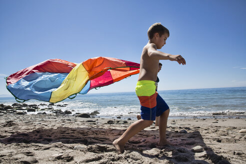 Mother and son running with multi colored textile on beach, County Park, Los Angeles, California, USA - ISF15827