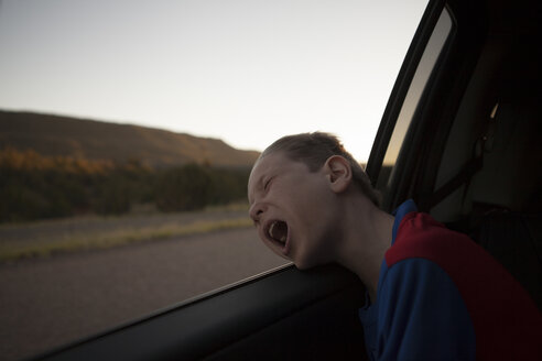 Boy leaning out of car window with eyes closed and mouth open - ISF15833