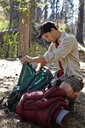 Young man in forest unpacking camping equipment, Los Angeles, California, USA - ISF15872