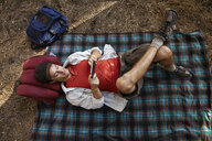 Overhead view of young male camper lying on picnic blanket in forest, Los Angeles, California, USA - ISF15884