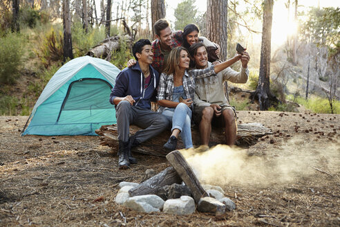Four young adult friends taking smartphone selfie by campfire in forest, Los Angeles, California, USA - ISF15887