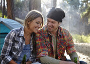 Young couple chatting by campfire in forest, Los Angeles, California, USA - ISF15890