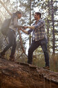 Young man giving girlfriend a helping hand on fallen tree in forest, Los Angeles, California, USA - ISF15896