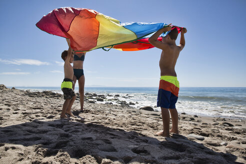 Mature woman and two sons holding up multi colored textile on beach, County Park, Los Angeles, California, USA - ISF15962