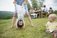 Female family member playfully holding toddler by legs at family gathering, outdoors - ISF16010