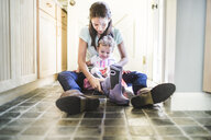 Mother and daughter putting on boots in kitchen - ISF16112