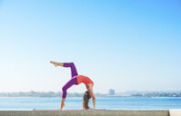 Young woman practicing yoga position at Pacific beach, San Diego, California, USA - ISF16148