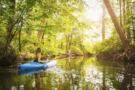 Young woman kayaking on forest river, Cary, North Carolina, USA - ISF16220