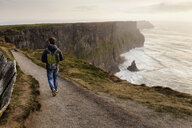 Mid adult man walking on The Cliffs of Moher, The Burren, County Clare, Ireland - ISF16289