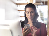 Portrait of smiling businesswoman using smartphone in office - ABRF00203
