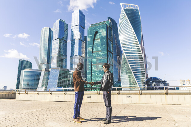 Russia, Moscow, two businessmen shaking hands in front of modern office buildings - WPEF00604