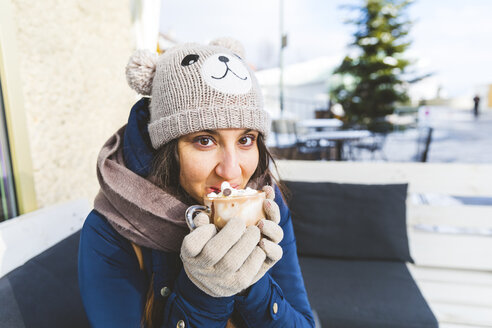 Portrait of woman drinking glass of hot chocolate with whipped cream - WPEF00618