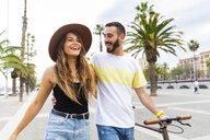 Spain, Barcelona, happy couple walking on seaside promenade - WPEF00621