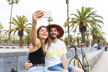 Spain, Barcelona, happy couple sitting on bench taking a selfie - WPEF00624