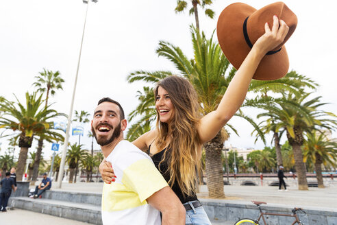 Spain, Barcelona, couple having fun on seaside promenade - WPEF00627