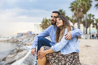Spain, Barcelona, couple sitting on rocks at the seaside - WPEF00633