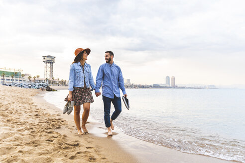 Spain, Barcelona, couple walking barefoot on the beach - WPEF00636