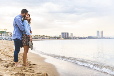 Spain, Barcelona, couple standing barefoot on the beach - WPEF00639