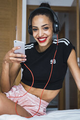 Portrait of smiling beautiful young woman sitting on bed with cell phone and headphones - KKAF01131