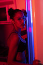 Portrait of beautiful young woman wearing bra and glasses in a dark illuminated room - KKAF01143