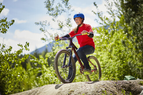 Young female bmx biker poised on edge of rock in forest - ISF16343
