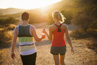 Joggers walking on sunlit path, Poway, CA, USA - ISF16361