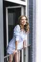 Smiling woman in pyjama at home looking out of balcony door - UUF14324