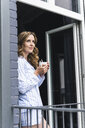 Smiling woman in pyjama at home with cup of coffee looking out of balcony door - UUF14327