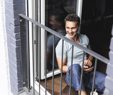 Smiling man in pyjama at home with cell phone looking out of balcony door - UUF14330