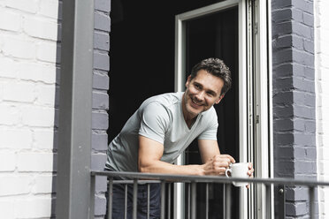 Smiling man in pyjama at home with cup of coffee looking out of balcony door - UUF14333